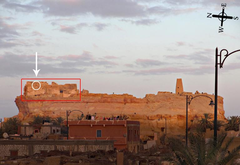 2.  The Aghurmi mound with the Temple of the Amun Oracle (red rectangle) as viewed from the west.  High in the top northwestern-most wall at the back of the temple, there is a very small, window-like opening (circled).