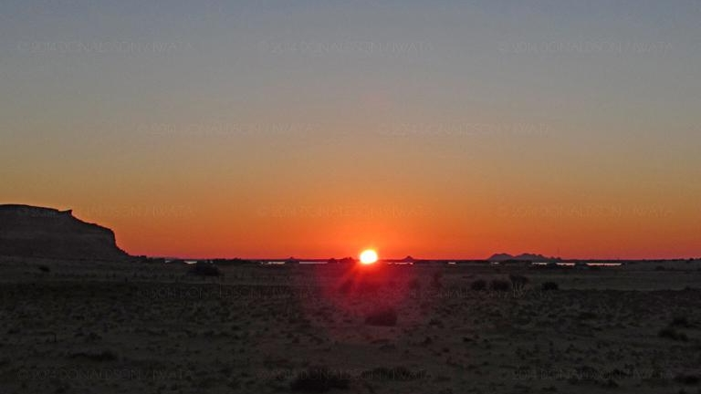 Spring equinox sunrise over the Amun Oracle/Aghurmi viewed from 12km away at Timasirayn temple in Siwa Oasis, Egypt on March 21st 2014.